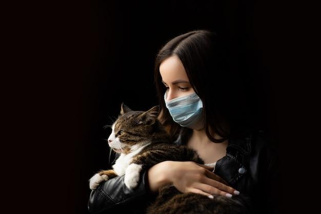 의료 마스크에 여자는 고양이를 보유하고있다.