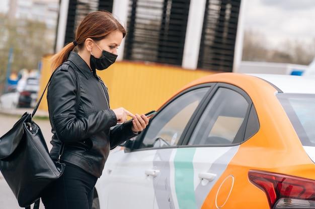Девушка в медицинской маске сдает машину для поездки в больницу. концепция безналичной оплаты в мобильном приложении
