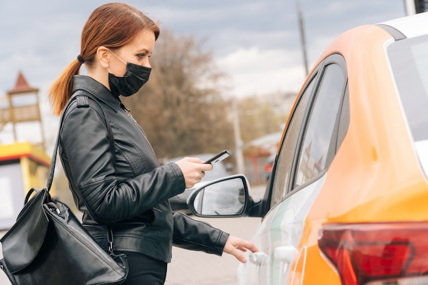 Девушка в медицинской маске сдает машину для поездки в больницу. концепция безналичного платежа в мобильном приложении