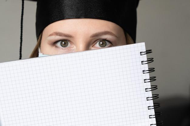 灰色の背景に彼女の顔の上にノートを保持している卒業式のガウンの帽子と医療マスクの女の子
