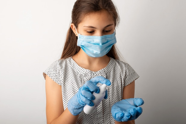 Девушка в медицинской защитной маске и перчатках наносит дезинфицирующий спрей на руки.