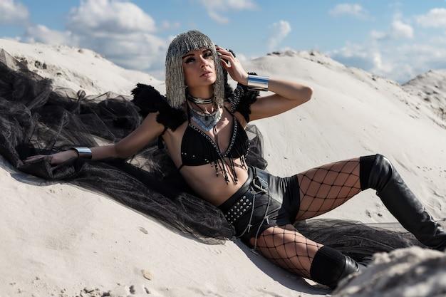 金属のかつらと黒のレトロな未来的なお祭りの衣装の女の子。