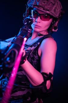 Девушка в военном комбинезоне страйкбол позирует с пистолетом в руках на темном фоне в дымке