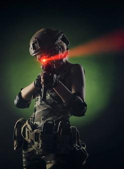 그녀의 손에 총을 들고 포즈 군사 특수 옷을 입은 소녀