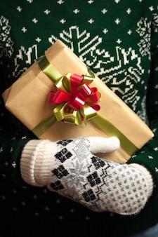 Девушка в варежках и свитер с зимним орнаментом держит рождественские подарки