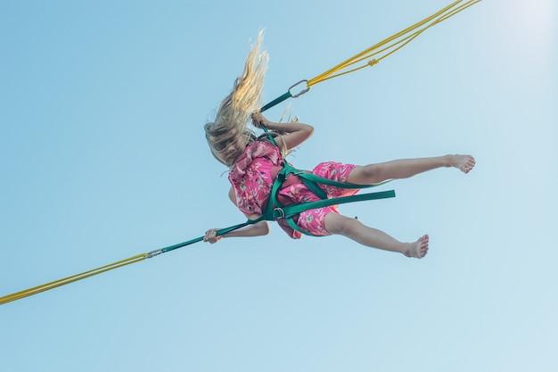 Девушка в разноцветном платье падает на аттракцион против неба.