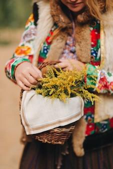 Девушка в национальном костюме с корзиной цветов крупным планом национальное платье