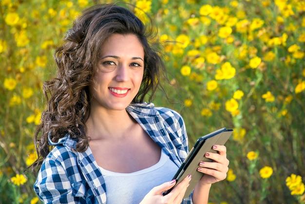 디지털 태블릿 미소를 사용하여 자연의 소녀