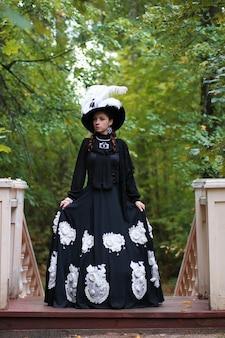 Девушка в старом ретро платье на лестнице на открытом воздухе