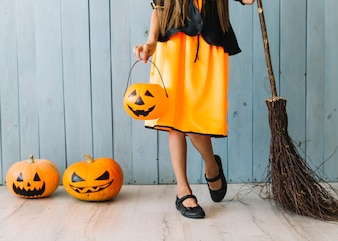 Girl in orange and black dress standing with Halloween basket and broom
