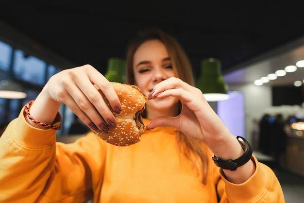 オレンジ色の服の女の子は手でおいしいハンバーガーを保持し、心のサインを示しています