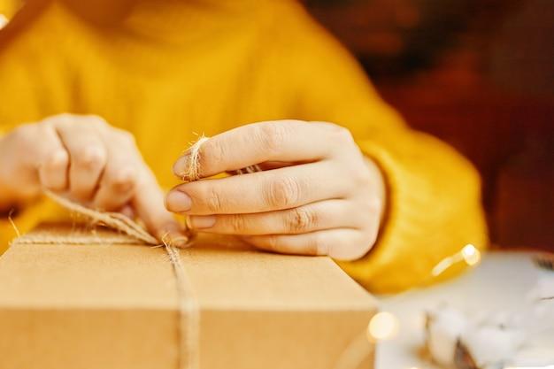 Девушка в оранжевом свитере завязывает шнурок на коробке упаковки подарков к празднику