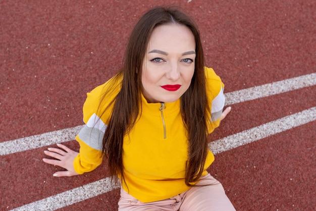 スタジアムのトレッドミルで、普通の服を着た女の子。あらゆる目的のために