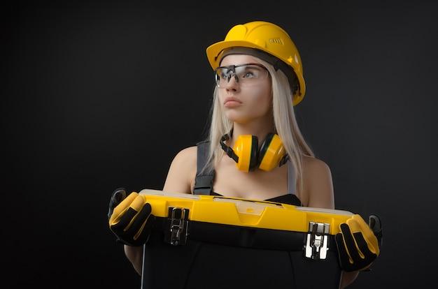 Девушка в комбинезоне держит чемодан с рабочими инструментами