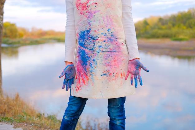 Девушка в окрашенные фартук с грязными руками. художница на природе