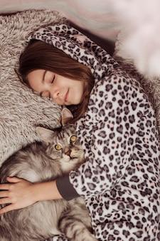Девушка в пижаме и вид сверху кошки