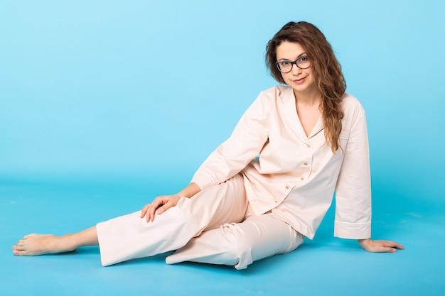 青い背景で家で休んでポーズをとるパジャマの女の子