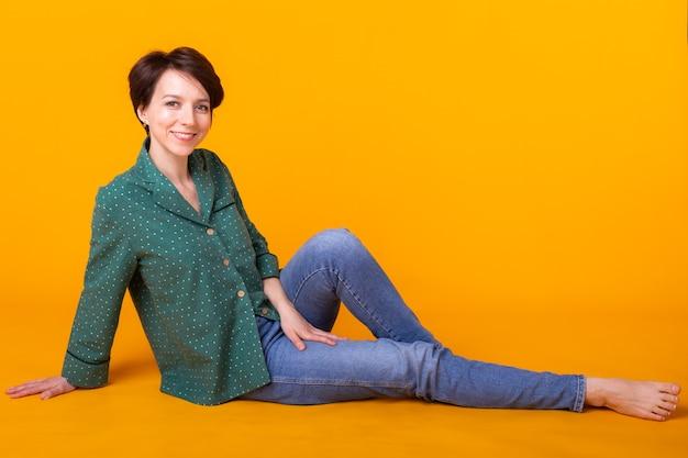 黄色の背景で家で休んでポーズをとるパジャマの女の子