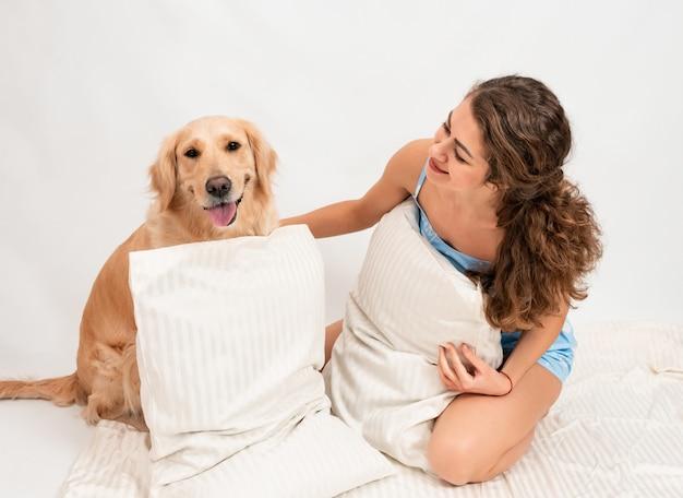 Девушка в пижаме с собакой, спрятанной за подушками на белом