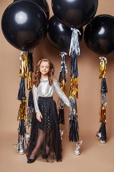 Девушка в праздничной одежде, модные черные воздушные шарики на бежевом