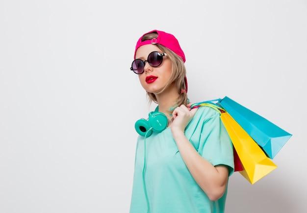 Девушка в розовой кепке и синей футболке с сумками