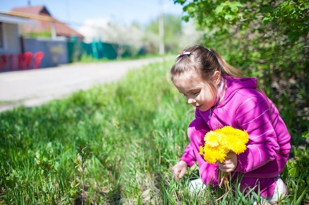 草の上に座って、夏の晴れた晴れた日に緑の自然に咲く黄色いタンポポの花を集めるピンクの衣装を着た女の子。幸せな子供時代の概念