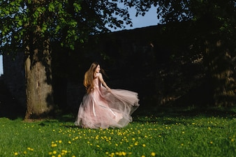 Girl in pink dress whirls on the green lawn before a castle wall in the rays of evening sun