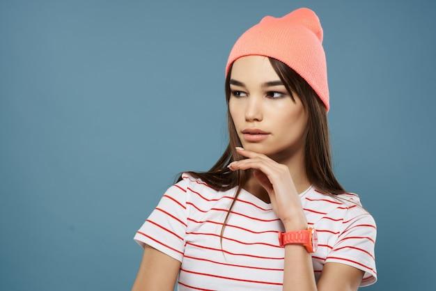 髪のファッション化粧品の夏のスタイルを保持しているピンクの帽子の女の子