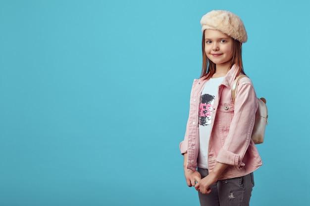 Девушка в розовой куртке и шляпе, взявшись за руки и улыбаясь