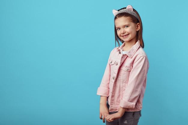 Девушка в розовой куртке и кошачьей повязке на голове, взявшись за руки и улыбаясь