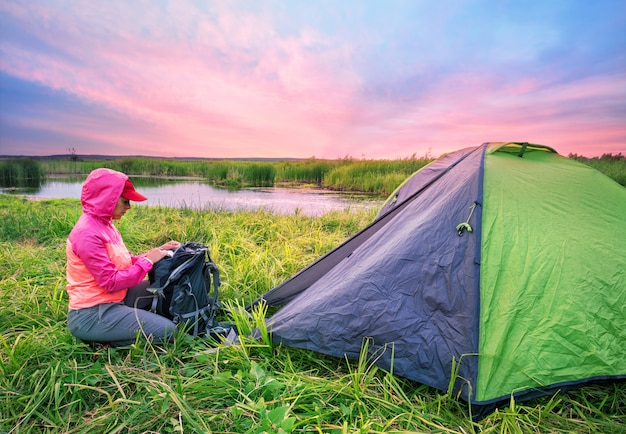 Девушка в розовом пиджаке открывает рюкзак возле палатки на берегу реки ба