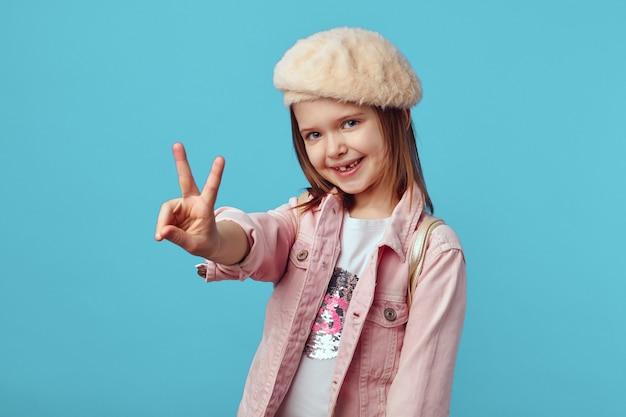 Девушка в розовой куртке очаровательно позирует и демонстрирует жест мира на синем фоне