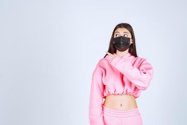 ピンクのパジャマと黒いマスクの後ろ側を指している女の子。