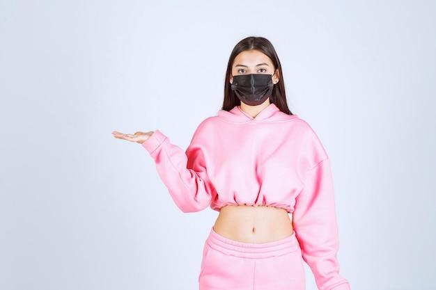ピンクのパジャマと左側を指す黒いマスクの女の子。