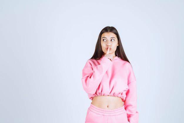 침묵을 요구하는 분홍색 잠옷 소녀