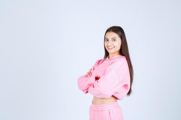 Девушка в розовой пижаме скрещивает руки и улыбается.