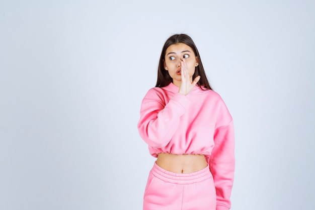가십을 하 고 분홍색 잠 옷에있는 여자