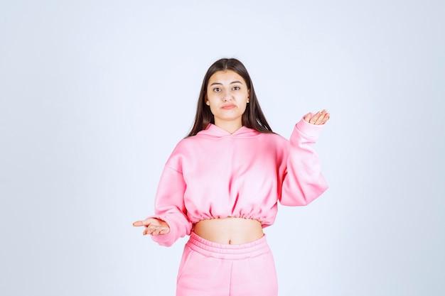 Девушка в розовой пижаме дает неудовлетворенные и нейтральные позы