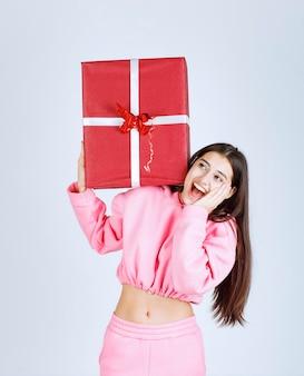 그녀의 머리 위에 큰 빨간 선물 상자를 들고 분홍색 잠옷 소녀.