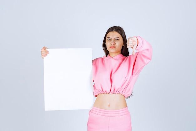 空白の正方形のプレゼンテーションボードを保持し、親指を下に見せているピンクのパジャマの女の子。