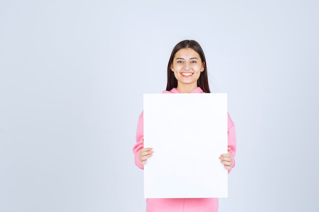 彼女の前に空白の正方形のプレゼンテーションボードを保持しているピンクのパジャマの女の子。