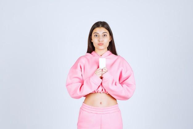 名刺を持ってビジネスパートナーに自己紹介するピンクのパジャマ姿の女の子。
