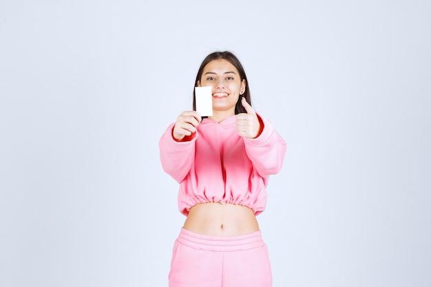 名刺を持って、楽しみの手のサインを示すピンクのパジャマの女の子。
