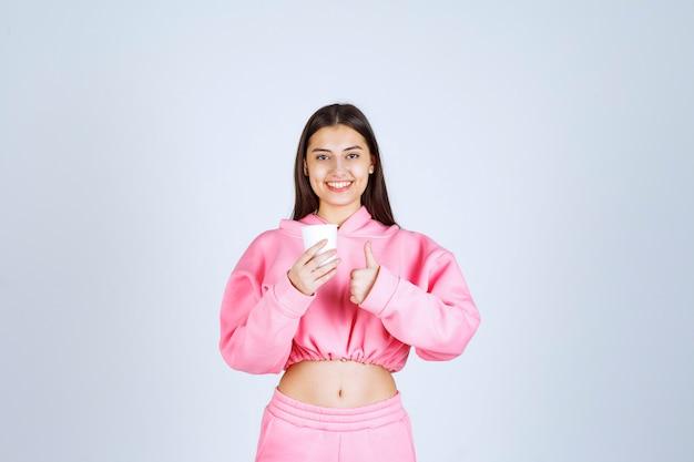 コーヒーカップを持って味を楽しんでいるピンクのパジャマの女の子