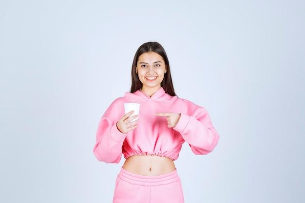 커피 컵을 들고 뭔가 가리키는 분홍색 잠옷 소녀