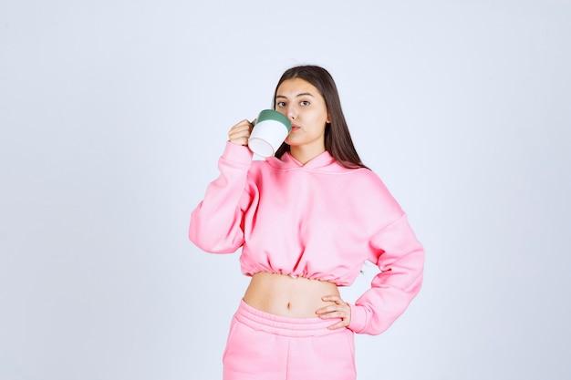 Девушка в розовой пижаме держит кружку кофе и пьет.
