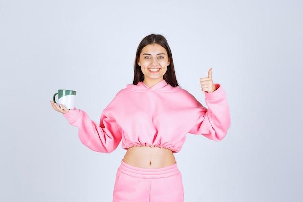 コーヒーマグを持って味を楽しんでいるピンクのパジャマの女の子。