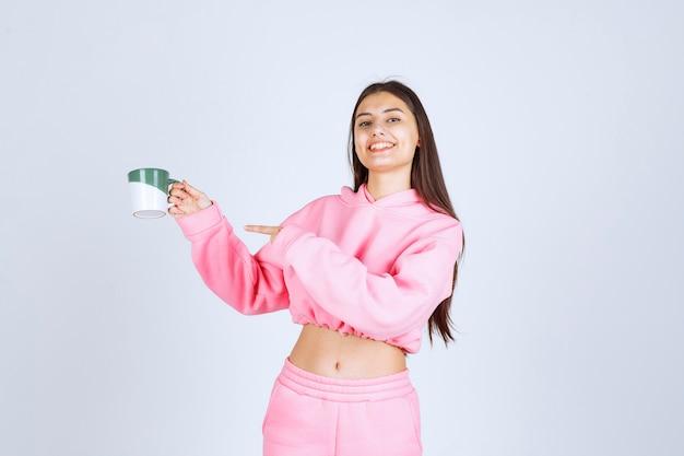 コーヒーのマグカップを持ってどこかを指しているピンクのパジャマの女の子。