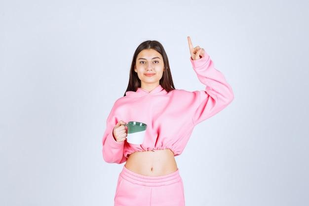 Девушка в розовой пижаме держит кружку кофе и указывает куда-то.