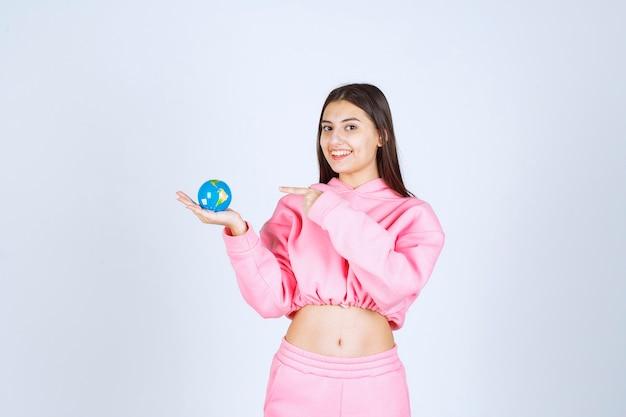 Девушка в розовой пижаме держит мини-глобус и указывает куда-то на него.